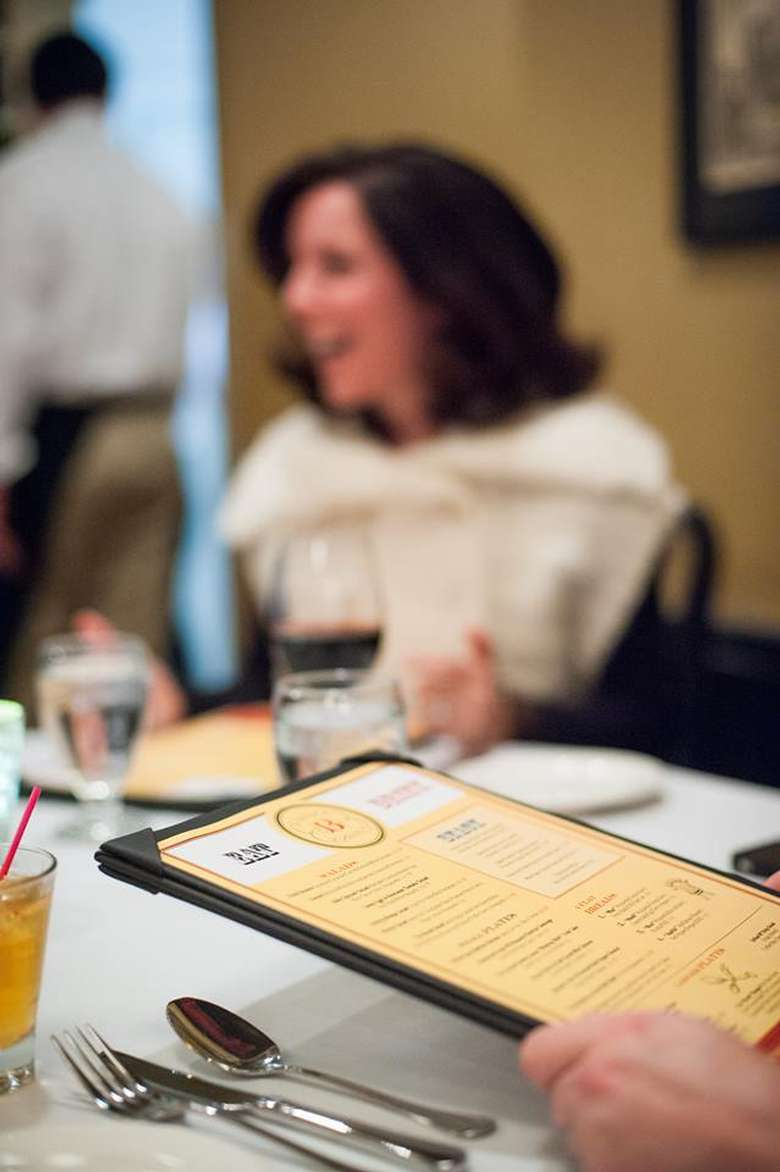 person reviewing a restaurant menu with a smiling woman in the background
