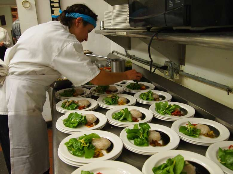 chef plating dozens of dishes for a large party