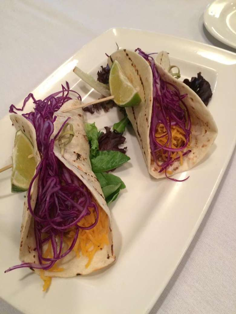 fish tacos on a plate with lemon wedges