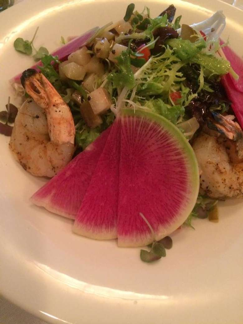 shrimp dish with greens and a sliced pink fruit