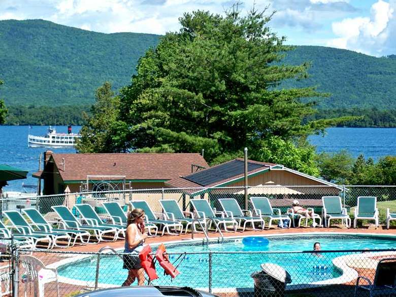 pool with lounge chairs and lake george in the background