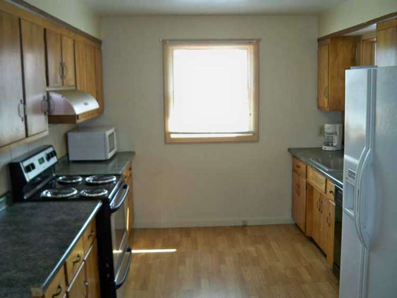 kitchen with brown cabinets, a black stove, and a white refrigerator