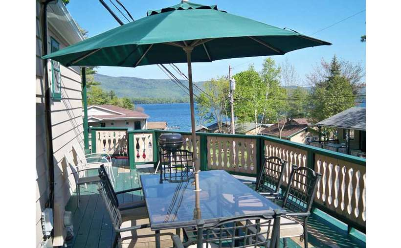 Patio table with umbrella on deck with views of Lake George