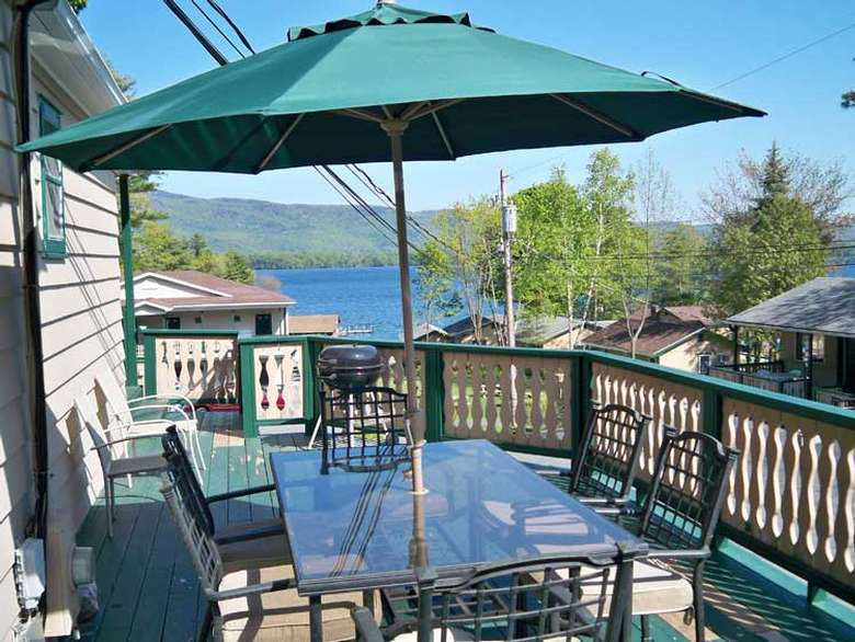 outdoor patio table with a green umbrella and lake george in the background