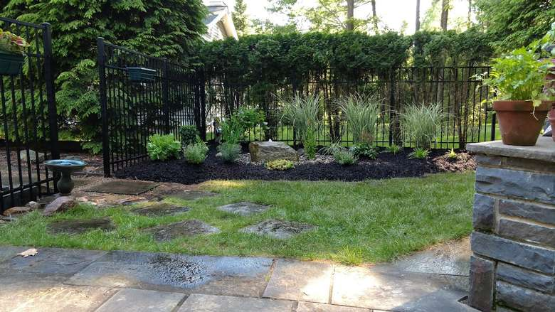 landscaped backyard area with tall grasses, other plants, and dark mulch