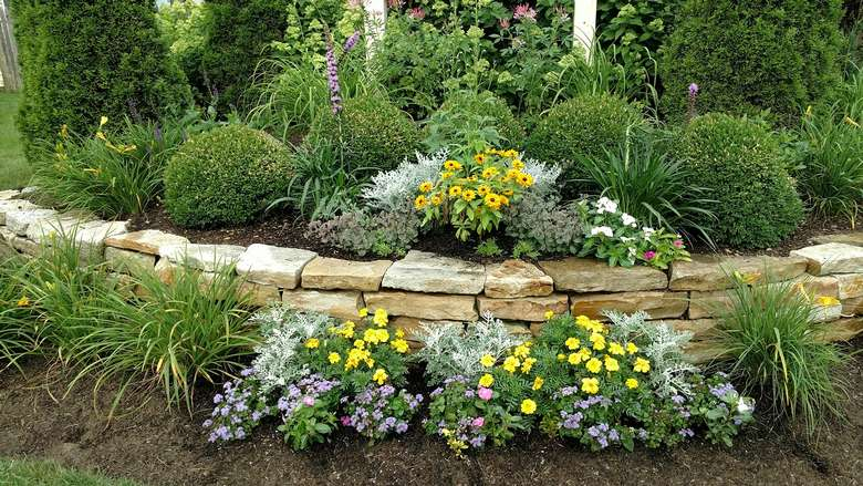 landscaped area in a yard with a stone wall, flowers, and other plants