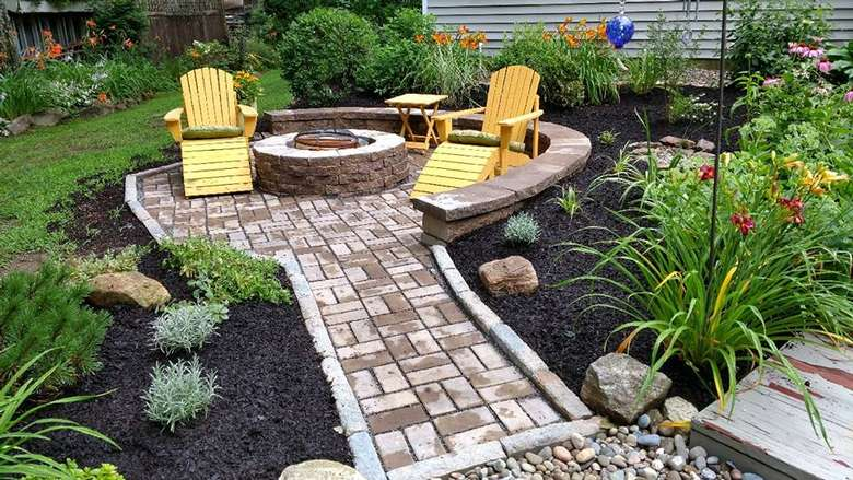 two yellow adirondack lounge chairs next to a fire pit on a stone patio