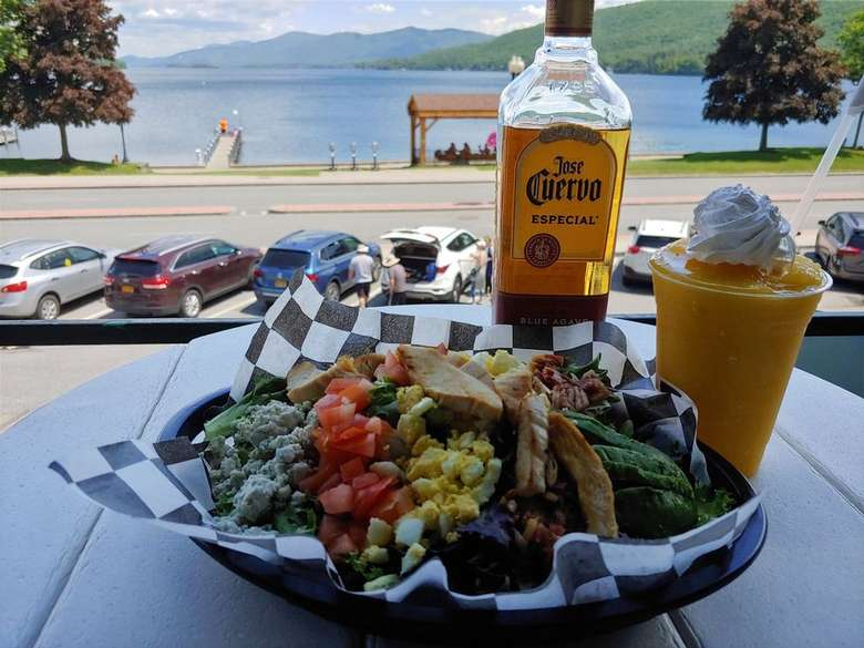 bottle of jose cuervo, a mixed drink, and a salad on a table