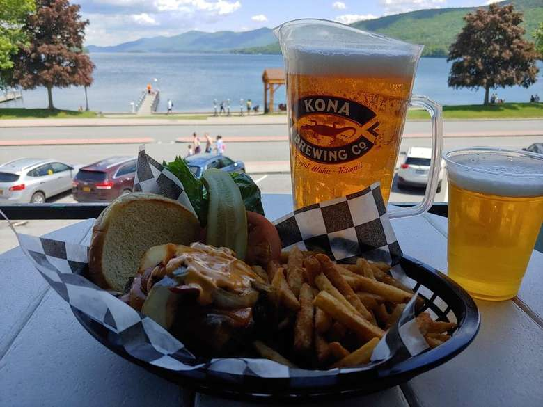 glass and cup of beer, a tray with fries and a burger