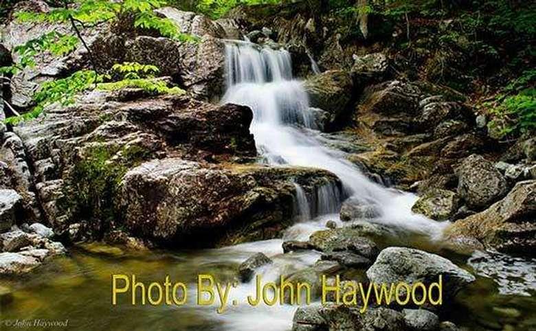 narrow waterfall running down multiple tiers of rocks