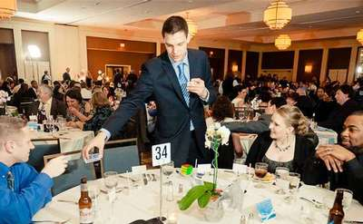 steven brundage handing a deck of cards to a dinner guest