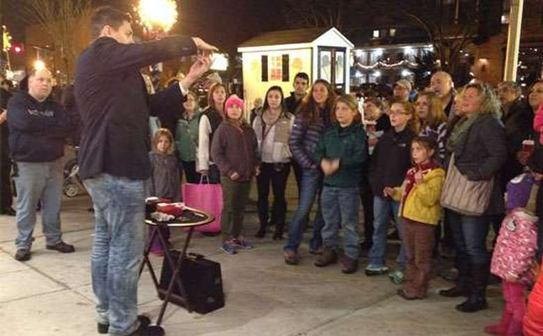 a crowd of people at night standing around as steven brundage performs a magic trick
