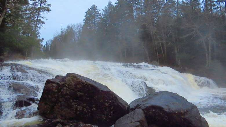 close-up of a waterfall flowing over rocks and mist rising up