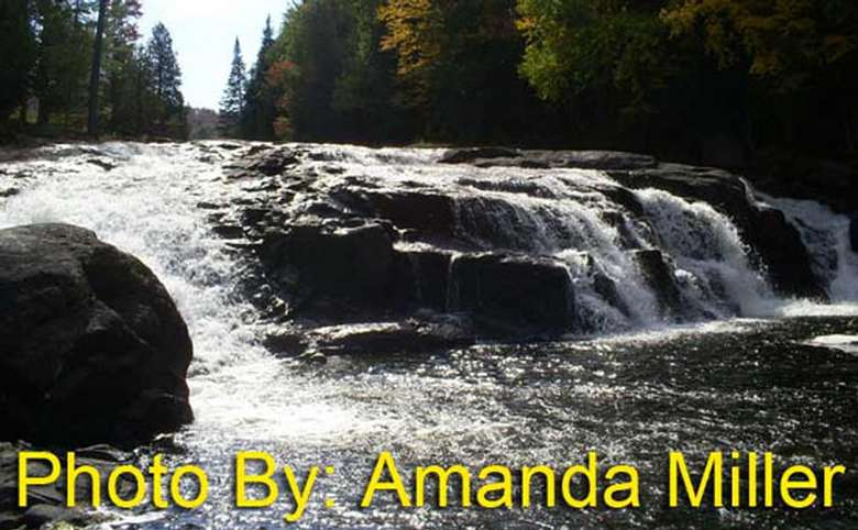 short, wide waterfall flowing over rocks with photo credit to amanda miller
