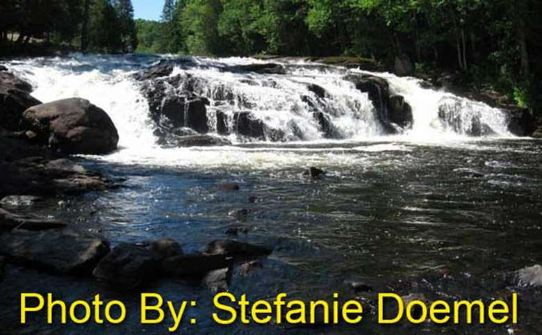 short, wide waterfall flowing over rocks with photo credit to stefanie doemel