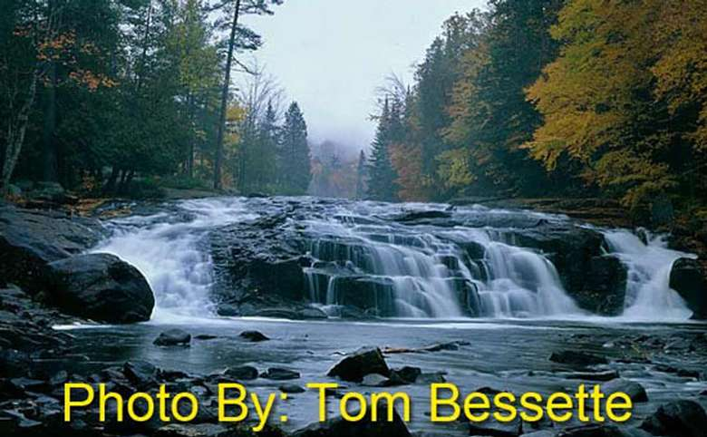 short, wide waterfall flowing over rocks with photo credit to tom bessette