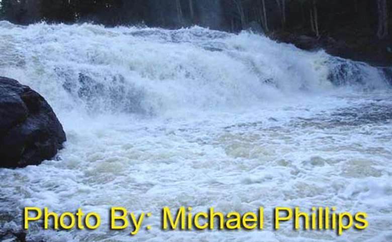 short, wide waterfall flowing over rocks with photo credit to michael phillips