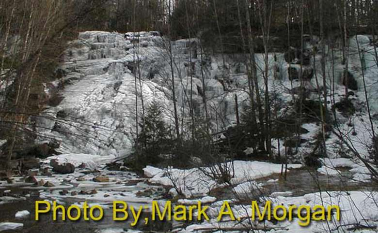 wide waterfall dropping down shallow tiers with photo credit to mark a. morgan