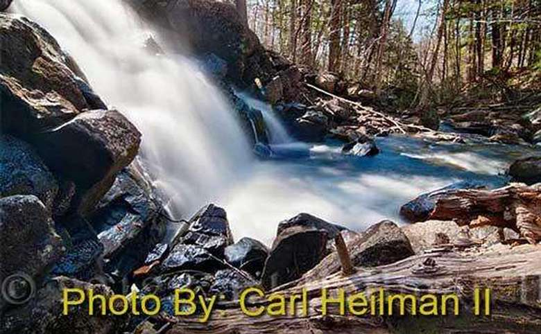 waterfall dropping into a pool with photo credit to carl heilman ii