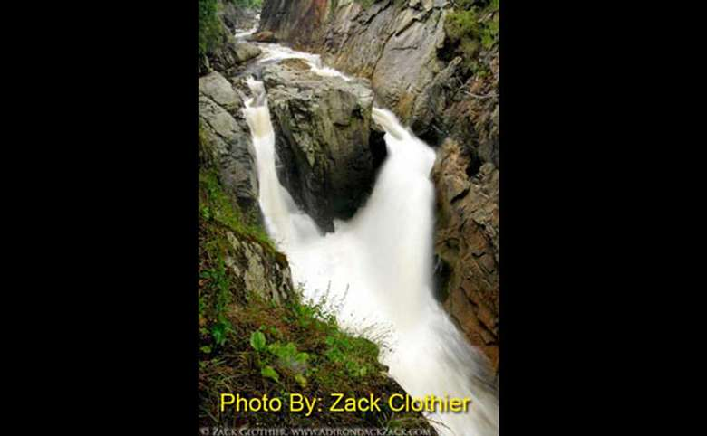 waterfall being split by a large rock and then coming back together with photo credit by zack clothier
