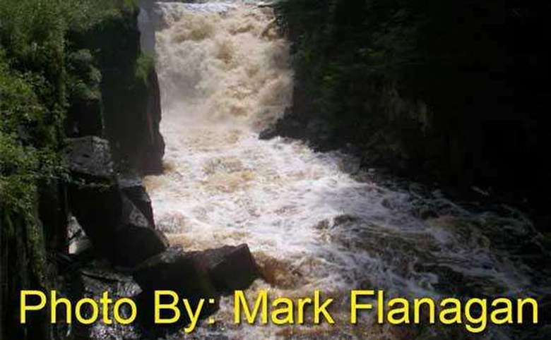 brown waterfall rushing into a pool with photo credit to mark flanagan