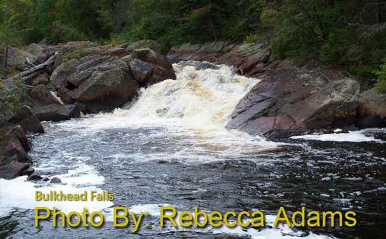 small waterfall rushing into a pool with photo credit to rebecca adams