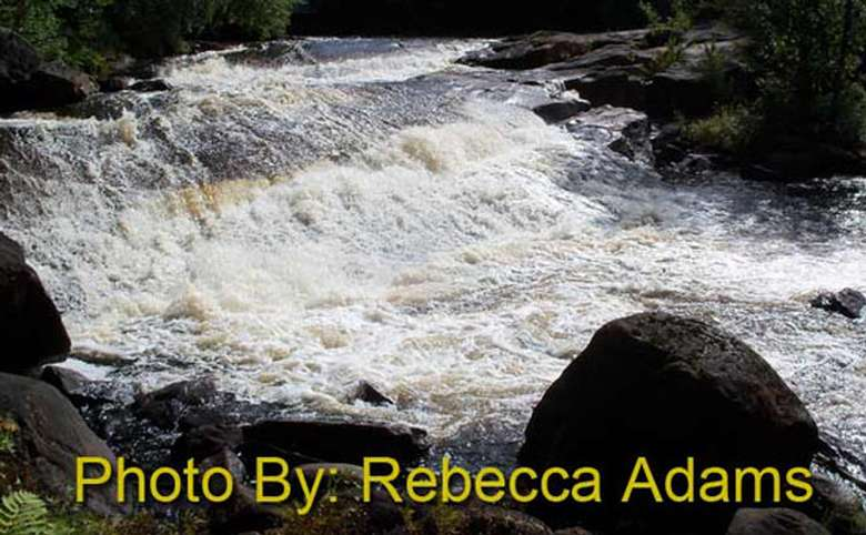wide, shallow waterfall dropping down a few tiers with photo credit to rebecca adams