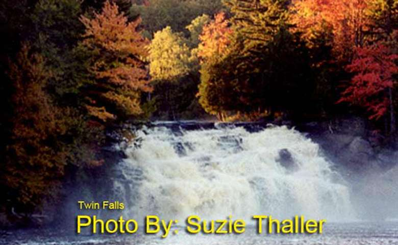 waterfall dropping multiple tiers with fall foliage surrounding it and photo credit to suzie thaller