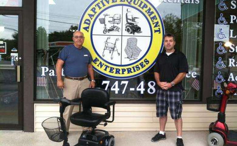 two men standing in front of the adaptive equipment enterprises storefront