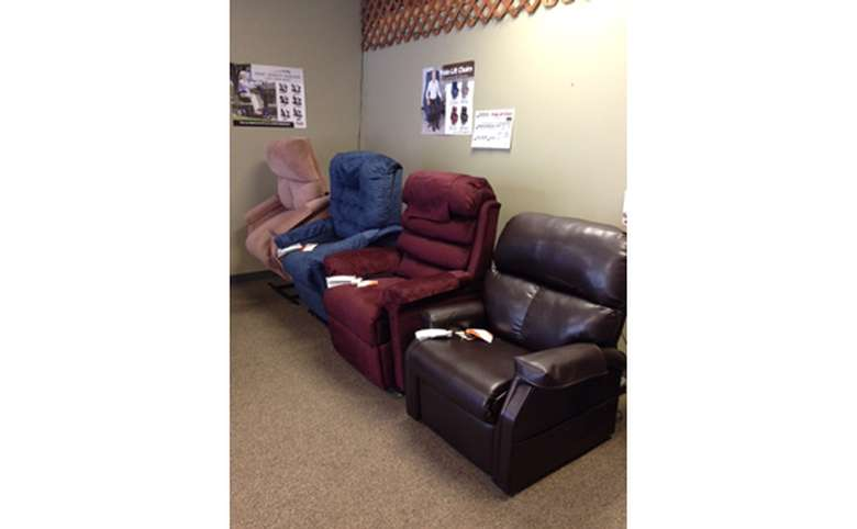 display of four recliners that can tilt forward to make it easier for people to stand up out of them