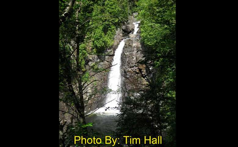 very steep narrow waterfall dropping into a pool with photo credit to tim hall