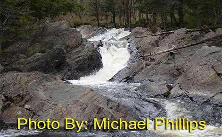 narrow, shallow waterfall winding between rocks with photo credit to michael phillips