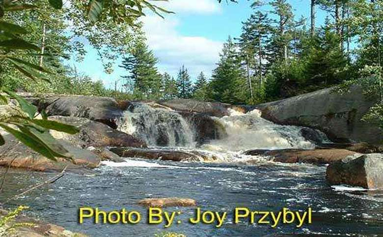 waterfall rushing over a large rock with photo credit to joy przybyl