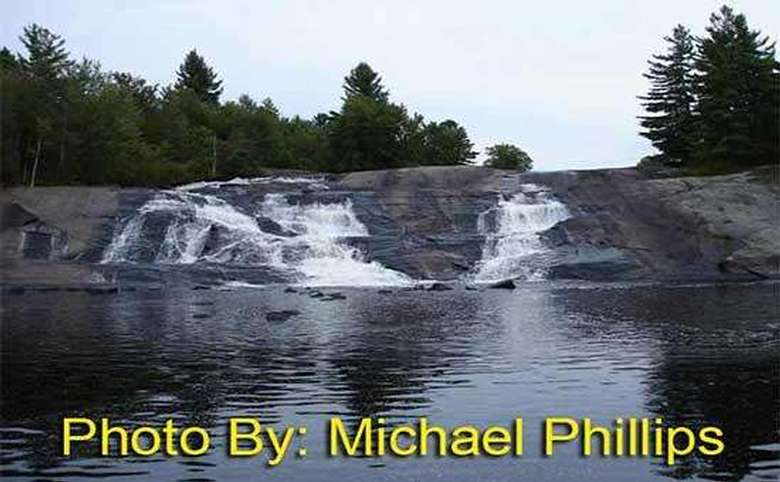 waterfall flowing down a rock face with photo credit to michael phillips