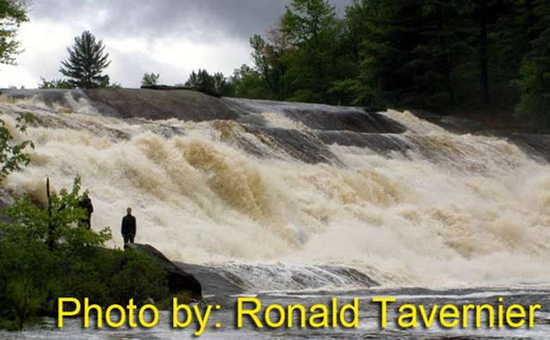 rushing waterfall flowing down a rock face with photo credit to ronald tavernier