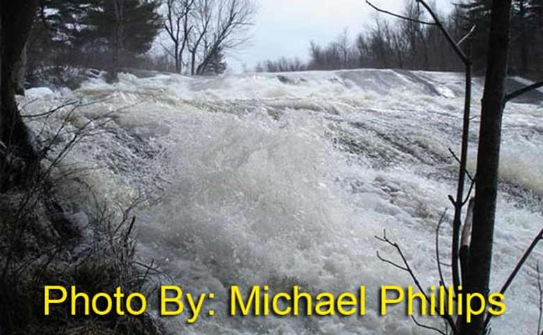 rushing waterfall flowing down a rock face with photo credit to michael phillips