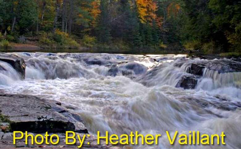 shallow rushing waterfall with photo credit to heather vaillant