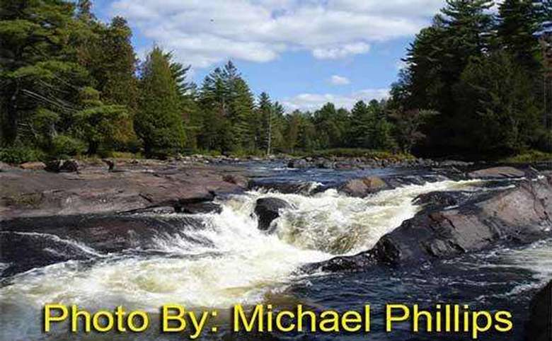small waterfall flowing over rocks with photo credit to michael phillips