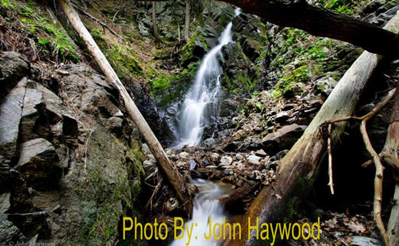 narrow waterfall dropping down rocks in the woods with photo credit to john haywood