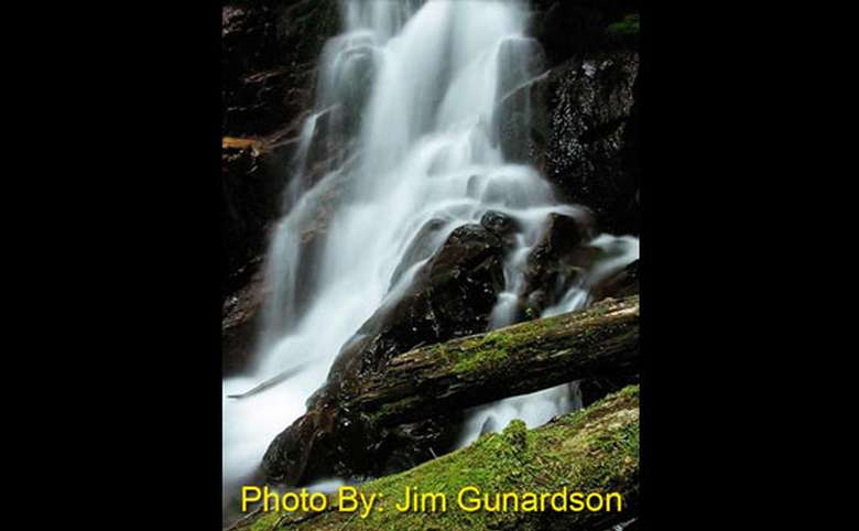 waterfall dropping over rocks and limbs with photo credit to jim gunardson