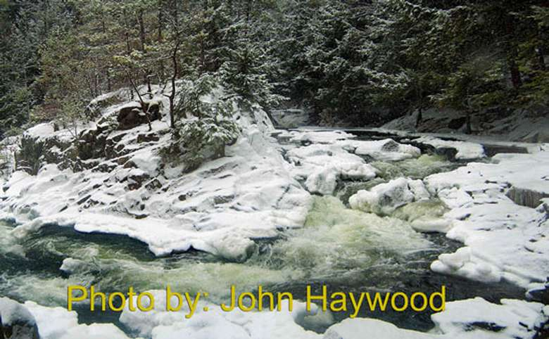 river flowing around rocks in the winter with photo credit to john haywood