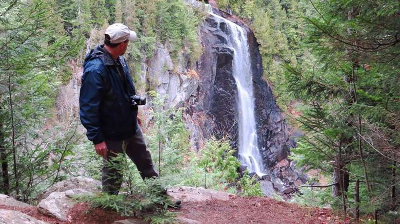 photographer looking behind him at a tall waterfall