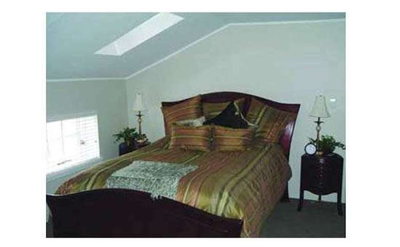 bed with a striped comforter in a room with sloped ceilings and a skylight