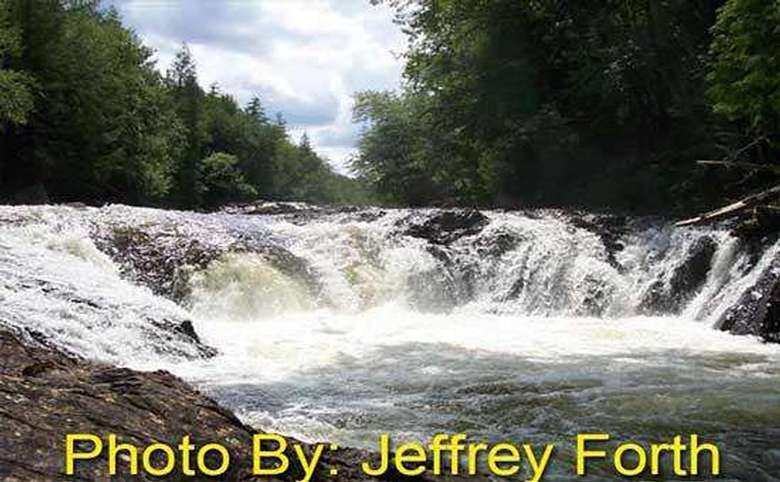 waterfall rushing over rocks with photo credit to jeffrey forth
