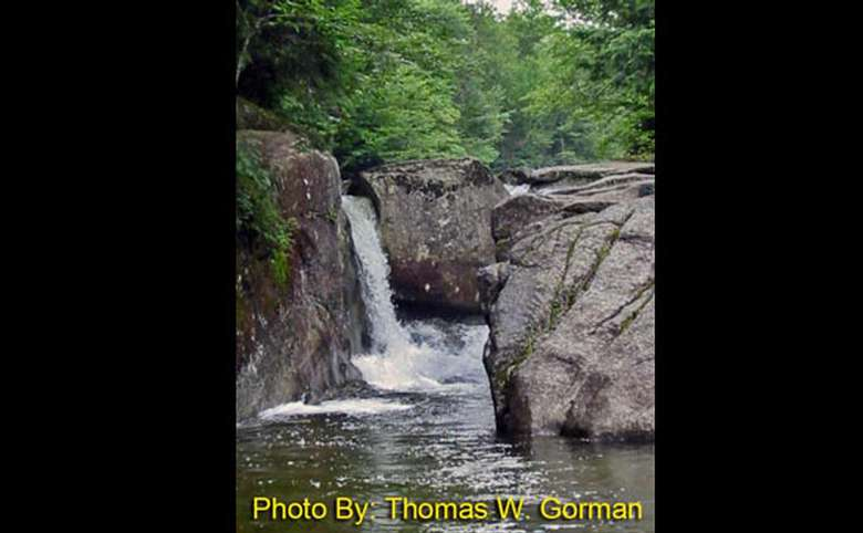 waterfall spouting between two rocks with photo credit to thomas w. gorman