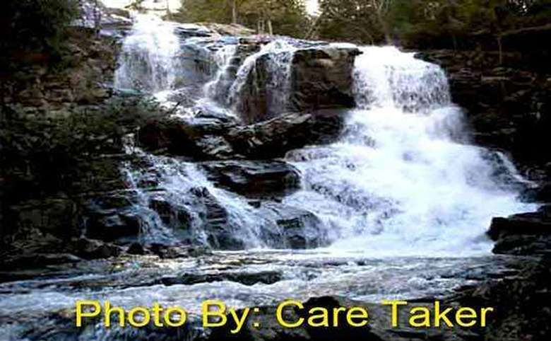 waterfall flowing over rocks with photo credit to care taker
