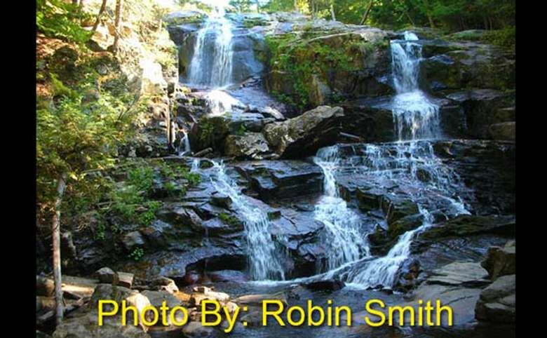 multi-tiered waterfall flowing over rocks with photo credit to robin smith