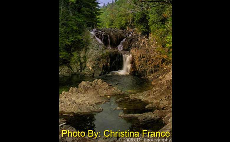 waterfall in the woods with photo credit to christina france
