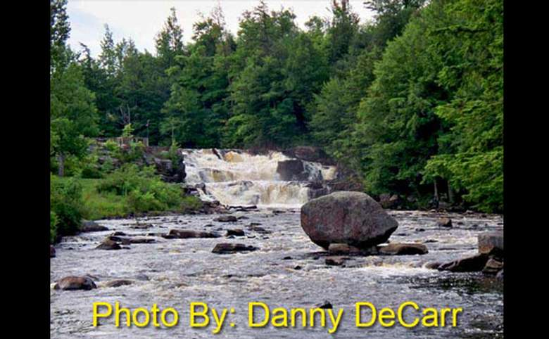 two-tiered waterfall flowing over rocks with photo credit to danny decarr