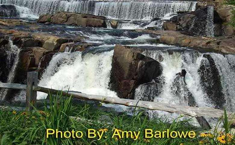 expansive waterfall flowing over multiple tiers of rocks with photo credit to amy barlowe